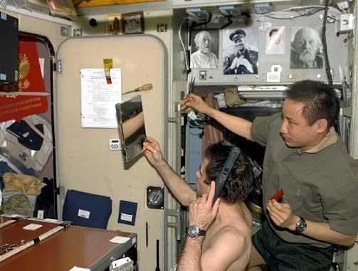 NASA ISS Science Officer Ed Lu cuts Commander Yuri Malenchenko's hair