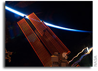 Photo: The Space Station's Solar Panels and a Crescent Earth 